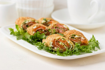 Roll pancakes with red fish and herb cream cheese.