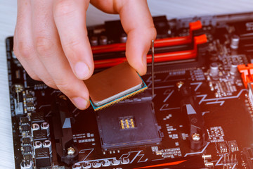 The technician is putting the CPU on the socket of the computer motherboard. the concept of computer hardware, repairing,