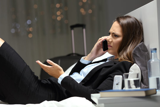 Angry businesswoman claiming on phone in an hotel room