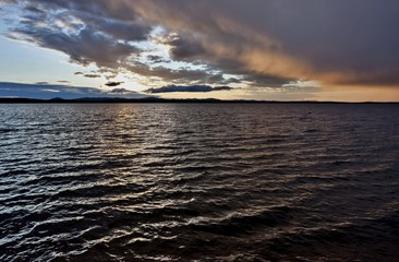 dark evening lake and orange clouds