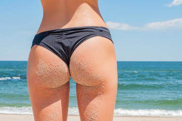 Beautiful tanned buttocks covered with sand on the beach
