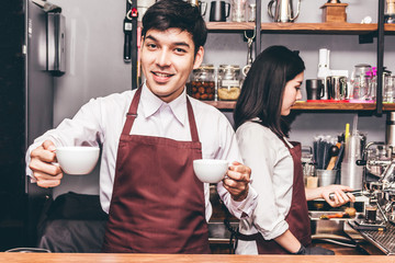 Portrait of couple small business owner smiling and working behind the counter bar in a cafe.Couple barista using coffee machine for making coffee at cafe