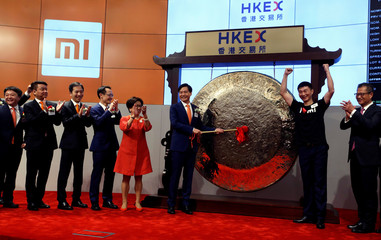 Xiaomi founder, Chairman and CEO Lei Jun hits the gong during the listing of the company at the Hong Kong Exchanges in Hong Kong