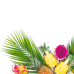 Frame of pineapple and dragon fruits with palm leaf on white background. Flat lay, top view. Tropical food concept.