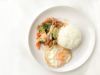 Fried Savory sauteed mixed vegetables with shimp and fried egg served with rice in white dish on white background as Thai homemade meal or recipe in the restaurant. Thai style food.