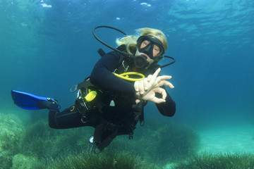 Female scuba diver okay signal