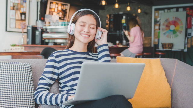 Young beautiful Asian woman working with laptop and listen music in coffee shop background.Concept of female freelancer.Vintage tone