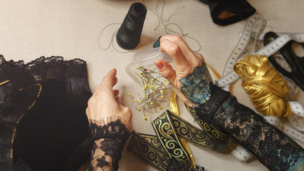 Girl is a fashion designer sewing an evening dress. Shooting close-up. She pours a set of pins out of the box.