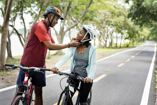 Man fastening the bike helmet for his girlfriend