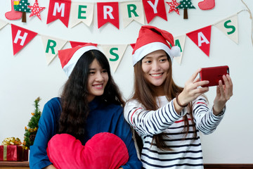 Two asian women selfie smart phone in Christmas party celebration, LGBT couple, friends Christmas party