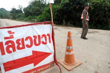 Police officers block a road leading to the Tham Luang cave complex in the northern province of Chiang Rai