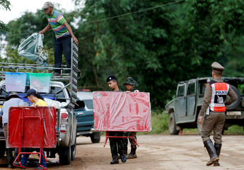 Soldiers and volunteers carry table near the Tham Luang cave complex in the northern province of Chiang Rai