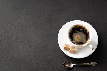 Black coffee cup with brown sugar on black concrete background. Business work desktop with coffee. Coffee break concept with copy space for text, top view