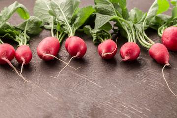 Fresh bunch of radish on wooden table.