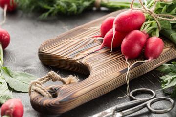 Fresh bunch of radish on a cutting board.