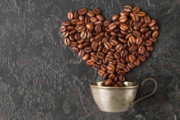 Heart shape of roasted coffee beans on dark background