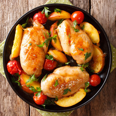 Glazed chicken fillet with peaches, tomatoes, onions closeup on a plate. top view from above
