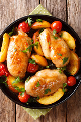 baked chicken breast with peaches, tomatoes, onions closeup on a plate. Vertical top view
