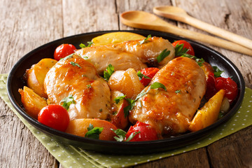 Summer food: chicken breast baked with fresh peaches, tomatoes, onions and honey garlic sauce close-up on a plate. horizontal