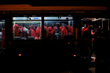 Migrants are seen in a bus moving towards a sports center after arriving on a rescue vessel at the port of Malaga