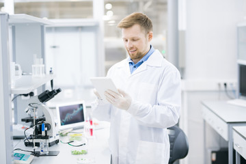 Waist up portrait of smiling young scientist wearing lab coat working on research using digital tablet, copy space