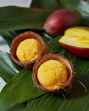 Mango ice cream sorbet in coconut peel with half fresh mango on palm leaves