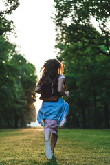 rear view of woman with backpack running on meadow with trees