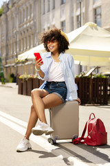 Next destination. Beautiful curly girl sitting on the suitcase and smiling while surfing the Internet on her smartphone and looking for the destination