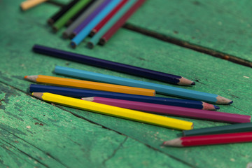 colorful pens on the green wooden table for school or education concept.