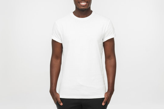 Young african american man standing with hands in pockets, wearing blank white t shirt with copy space for your logo or text, isolated on grey background