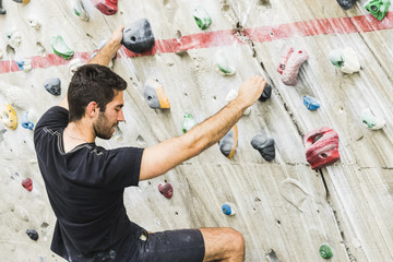 Man practicing rock climbing on artificial wall indoors. Active lifestyle and bouldering concept..