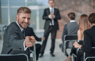 businessman sitting in the conference room, pointing at you