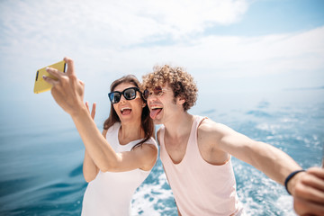 Happy caucasian couple taking selfie photo over beautiful sea background. Romantic lovers, woman and man traveling on yacht sailing vacation.