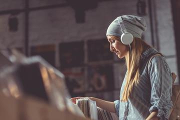 Spoed Foto op Canvas Muziekwinkel Young girl with headphones in a music store