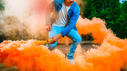 a young man in a blue jumpsuit t is holding a smoke bomb in his hands. A man is holding colored orange smoke