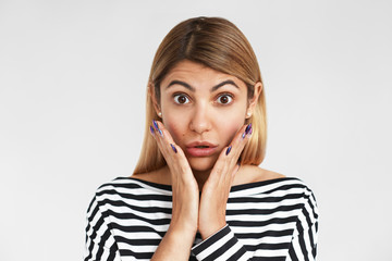 Horizontal shot of attractive bug eyed young blonde Caucasian woman wearing stylish striped t-shirt keeping hands on cheeks and raising eyebrows, shocked with big sale prices or unbelievable gossip