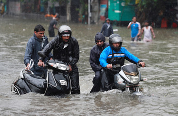 A man pushes his scooter as another rides his motorcycle through a waterlogged street during heavy rains in Mumbai