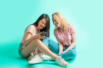 Social media, technology, friendship, sport and health, body positive emotions and people concept - smiling interracial female couple summer clothes reading funy stories smartphoone, blue background