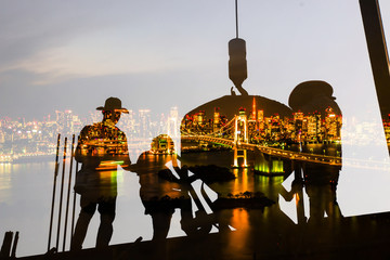 Double exposure of worker in construction with rainbow bridge in the night