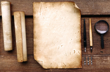 Vintage writing set with old paper on brown wood texture with feather and ink