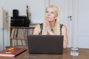 Thoughtful blond woman sitting pondering a problem
