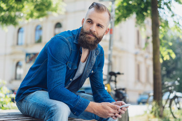 Young bearded man in denim shirt sitting on bench