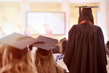 Woman in special black robe and cap standing and waiting for receiving diploma during official ceremony