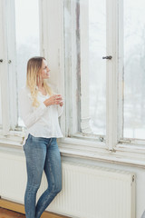 Slender woman in jeans staring out of a window