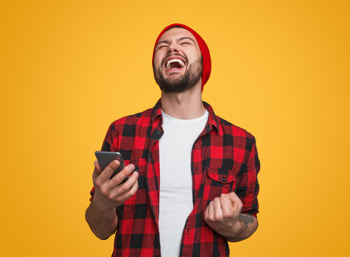 Happy male with smartphone celebrating success