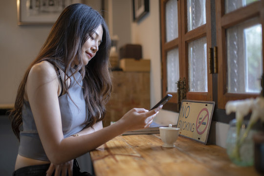 Asian women check cell phone information in coffee shop