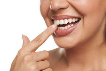 young woman touchng her teeth with her finger on white background