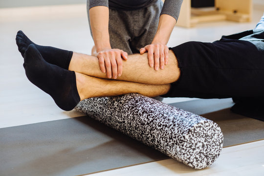 Close up of man's legs using a foam roller on the ground, Female coach rehabilitation specialist helping young handsome man doing exercise with back surface shin. Rehabilitation after trauma concept.
