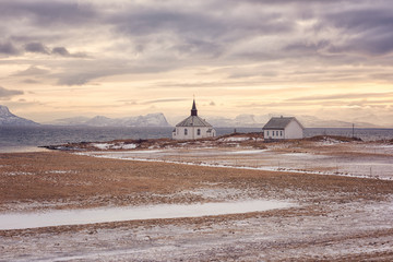 Beautiful winter sunset landscape, panoramic view with white lonely church and house on the Atlantic coast, Lofoten Islands, Norway