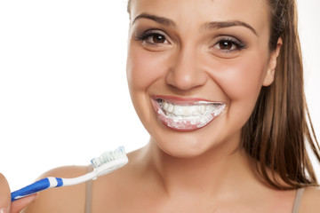 young happy woman brushing her teeth on white background
